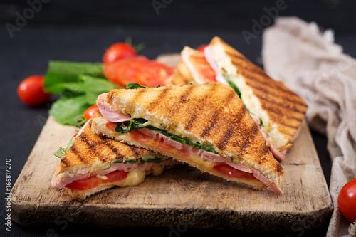 Club sandwich panini with ham, tomato, cheese and basil.
