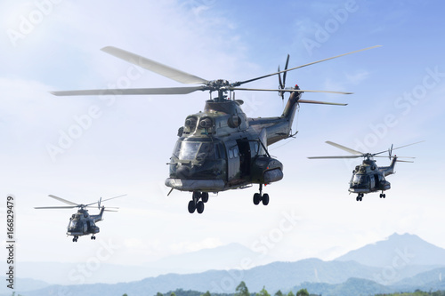 Three military helicopters patrolling in the mountain