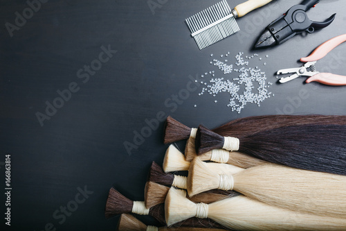 Set of sevral color hair extension tools on a dark background Fototapeta