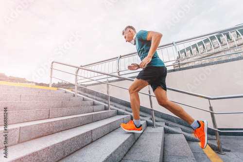 healthy lifestyle middle aged man runner running upstairs on city stairs. vintage color