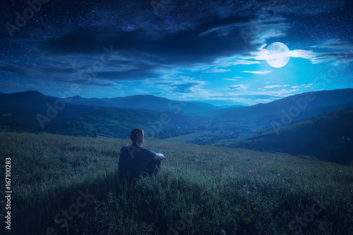 Photo Human sitting on a hill in and enjoy moon rising