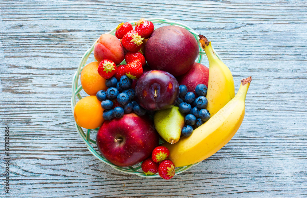 Bowl of fresh fruit with banana, apple, strawberries, apricots, blueberries, plums, whole grains, forks, top view <span>plik: #167103886 | autor: bessapics</span>