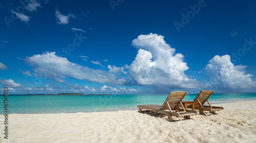 Empty wooden beach chairs on the tropical beach, vacation. Traveler dreams concept