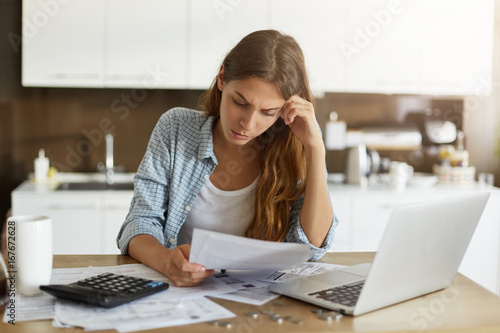 Billede på lærred Attractive young housewife wearing shirt at home studying gas and electricity bi