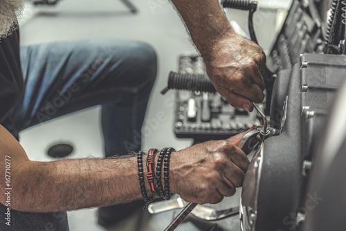Fotomural Old man using wrench for repair