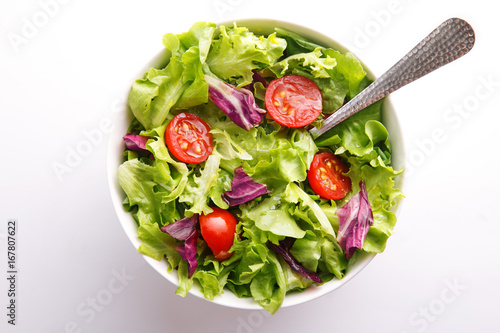 Fresh salad in a bowl. Healthy lettuce and tomato meal on a white background. Top view