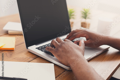 Slika na platnu African-american businessman in office type on laptop