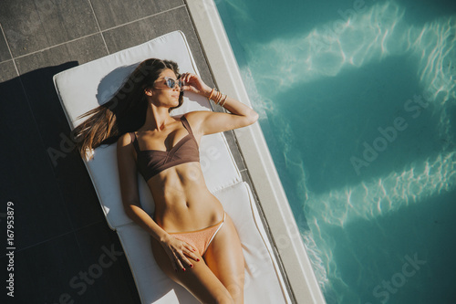 Tableau sur Toile Young woman lying by the pool on sunbed