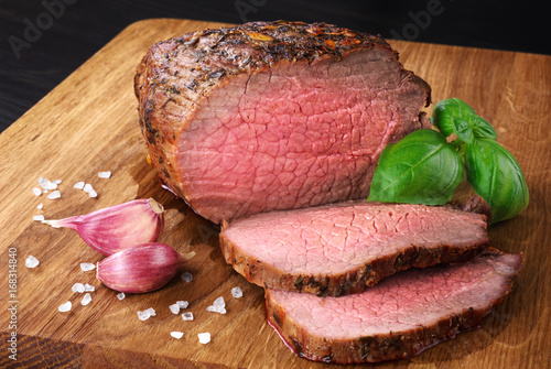 Photo Baked meat, garlic and basil on a wooden background. Roast beef.
