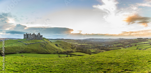 Photo Countryside panorama with ruined castle on a hill at sunset