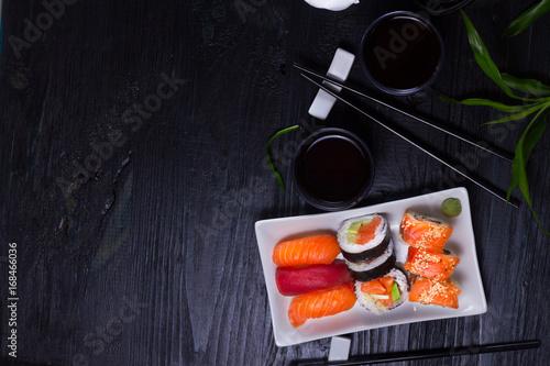 Obraz na plátně Japanese sushi dish with tea and chopsticks on black wooden background with copy