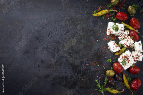 Traditional Greek Feta with Vegetable and peperoni as top view with copy space on an old rustic board