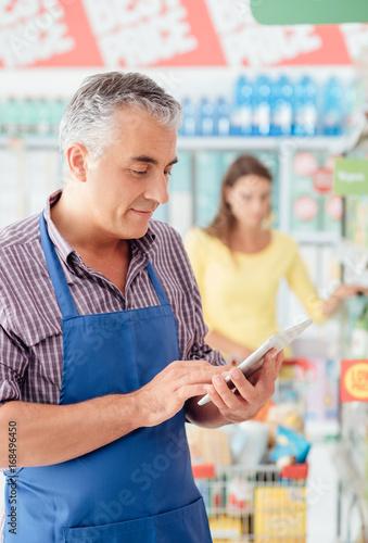 Carta da parati Supermarket clerk using a tablet