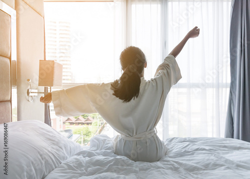 Valokuvatapetti Easy lifestyle young Asian girl waking up in the morning taking a rest relaxing