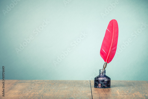 Vintage old red quill pen with inkwell on wooden table front gradient mint green wall background. Retro style filtered photo