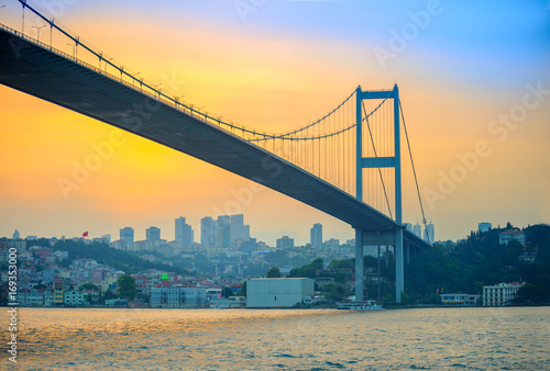 bridge through the Bosphorus strait in the evening on a sunset, on a background Fototapet