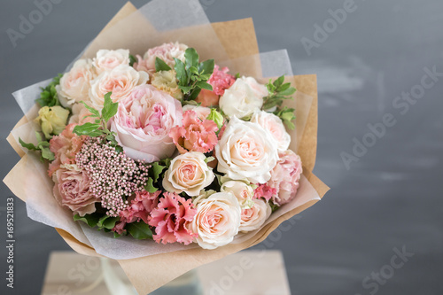 Fotografia, Obraz Bouquet in kraft paper. A simple bouquet of flowers and greens