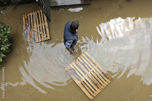 Photo The consequences of flooding, man in the water helping neighborhood