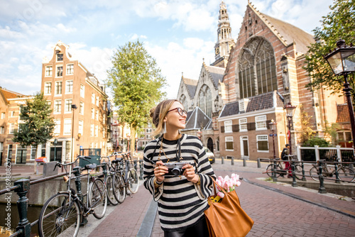 Fototapeta premium Młoda kobieta turystycznych stojących z aparatem fotograficznym na moście w pobliżu starego kościoła w godzinach porannych na starym mieście w Amsterdamie