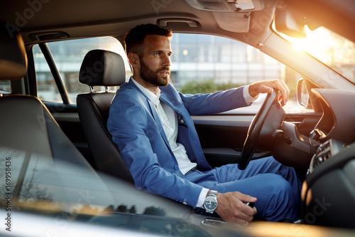 Fotografiet Attractive man in business suit driving car.