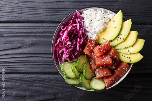 Raw Organic Ahi Tuna Poke Bowl with Rice and Veggies close-up. Horizontal top view