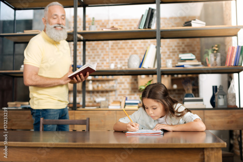 Slika na platnu Joyful grandfather dictating words to his granddaughter