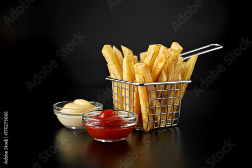 Fotografia French fries in basket with ketchup and sauce isolated on black background