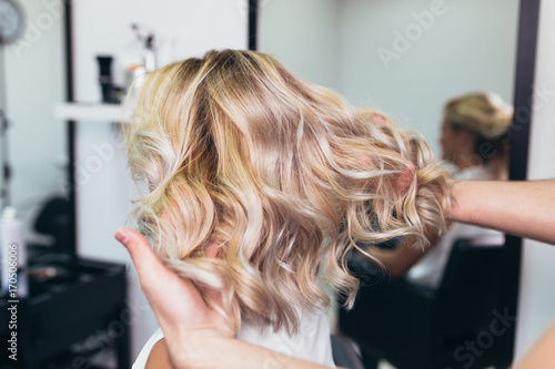 Valokuvatapetti Beautiful hairstyle of young woman after dying hair and making highlights in hair salon