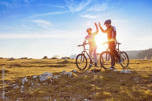 szczęśliwa para idzie na górską asfaltową drogę w lesie na rowerach z hełmami, dając sobie piątkę
