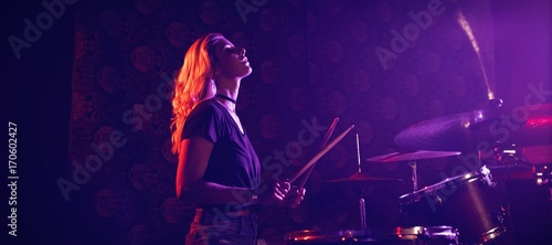 Fotografering Young female drummer performing in illuminated nightclub