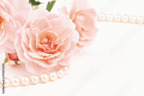 Close up of pearl necklace and pink roses