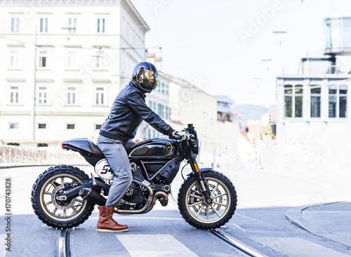 Valokuvatapetti Motorcycle rider on custom made scrambler style cafe racer in the city
