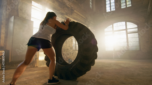 Fotografia, Obraz Fit Athletic Woman Lifts Tire as Part of Her Cross Fitness/ Bodybuilding Training