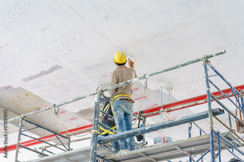 Canvas Print Construction workers on scaffolding tower painting and renovating building floor in construction site