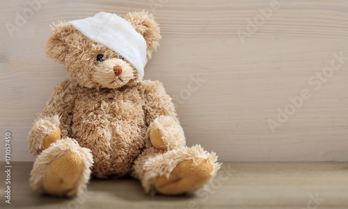 Fotografie, Tablou Teddy bear with bandage on a wooden floor