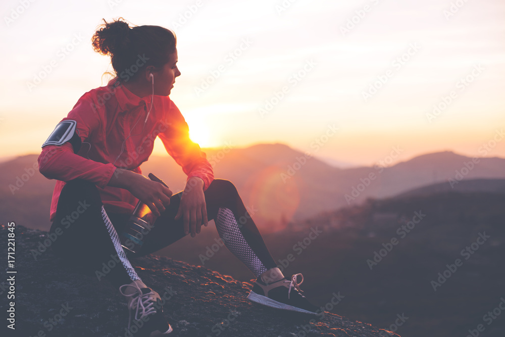 Athletic woman resting after a hard training in the mountains at sunset. Sport tight clothes.