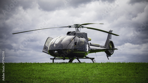 Fotografia Black helicopter standing on the green grass