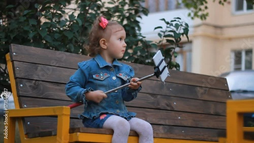 cute funny beautiful little girl sitting on bench in park and doing selfie on white mobile phone. A child makes a selfie photo. Stock Video | Adobe Stock