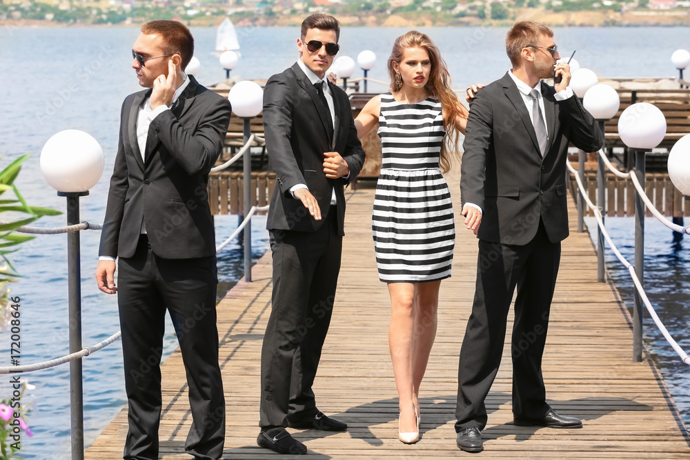 Young celebrity with bodyguards outdoors <span>plik: #172008646   autor: Africa Studio</span>