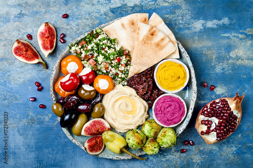 Fototapeta Middle Eastern meze platter with green falafel, pita, sun dried tomatoes, pumpkin and beet hummus, olives, stuffed peppers, tabbouleh, figs
