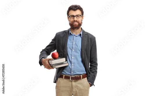 Teacher with an apple and books looking at the camera Fototapeta