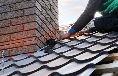 Roofer builder worker attach metal sheet to the chimney Fototapet