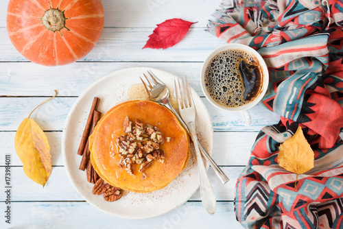 Pumpkin pancakes with pecan nuts, honey and cup of coffee. Autumn food composition on white table. Top view, flat lay composition