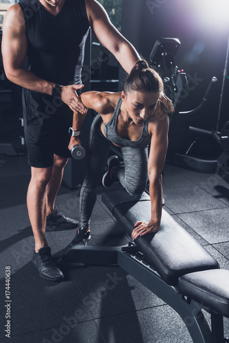 Fotografia trainer helping woman to exercise with dumbbell