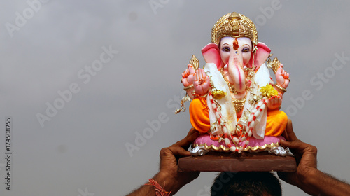 Hands holding Ganesha idol before immersion in water tank, annual ritual, during Ganesha Chathurthi Hindu festival