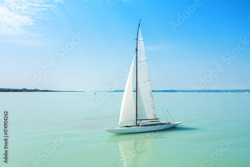 Obraz na plátně A view from a ship to bright Balaton lake water and a white yacht on sunny summer day, Hungary