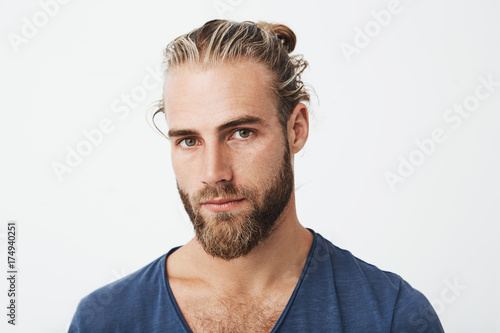 Stampa su Tela Close up of beautiful young man with stylish hairstyle and beard in blue t-shirt looking with serious expression in camera
