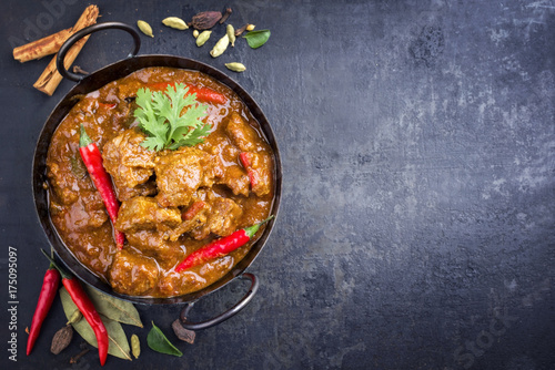 Valokuvatapetti Traditional Indian curry lamb masala as close-up in a Korai with copy space righ