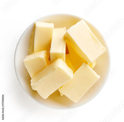 Butter pieces in bowl isolated on white background, top view