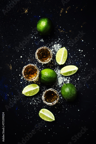 Golden mexican tequila with lime and sea salt, black background, top view
